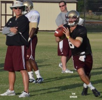 Senior quarterback Duke DeLancellotti rolls out under the close supervision of co-offensive coordinator Mike Schultz.