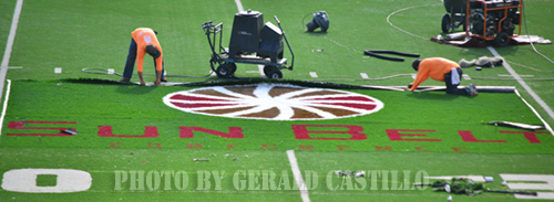 Workers at Bobcat Stadium put in the Sun Belt Conference logo.