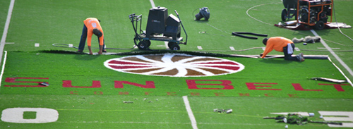 Workers place the Sun Belt logo inside Bobcat Stadium this summer.